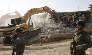 A Caterpillar bulldozer razes a Palestinian building in the West Bank.