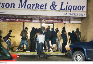 Rioters in Ferguson looted a local liquor store. Several businesses burned during the rioting, which also saw the destruction of two police cruisers.