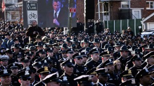 NYPD officers turn their backs on a video of New York Mayor Bill de Blasio at the memorial service for slain officer Rafael Ramos.