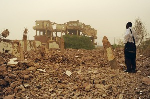 Fourteen years after the fact, a Sudanese man gazes at the wreckage of the Al-Shifa pharmaceutical plant.