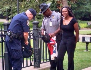 Bree Newsome smiles for a job well done during her arrest. Notice the black officer balling up the flag in his hands, as if unconsciously regretting he had to make the arrest at all.
