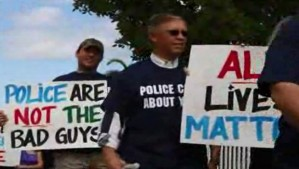 Protesters carry signs insisting all lives matter.